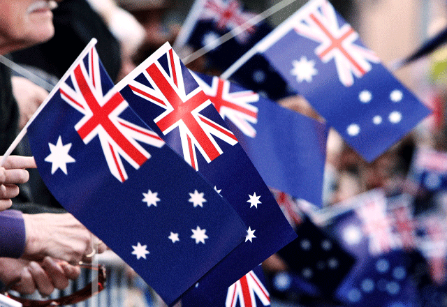 Australian flags being waved at a parade.