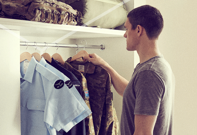 Man choosing a shirt from a rack.